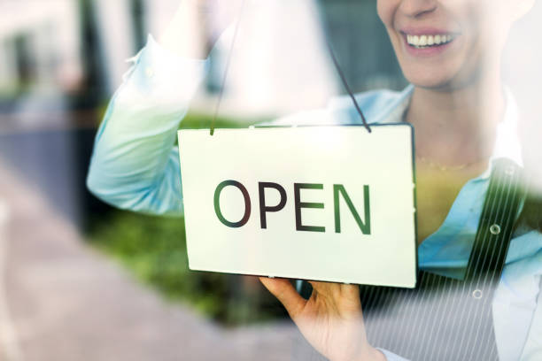 woman holding open sign in cafe - open sign stock pictures, royalty-free photos & images