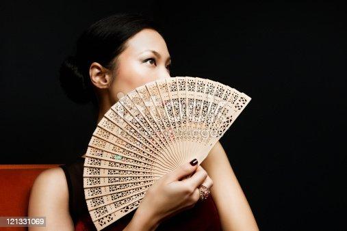 istock Woman holding oriental fan, portrait 121331069