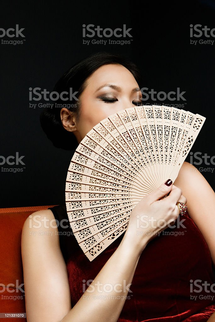 Woman holding oriental fan, portrait stock photo