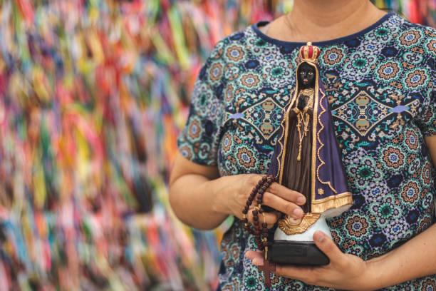 Mulher segurando a imagem de nossa senhora da Conceição Aparecida estatueta e um rosário. - foto de acervo