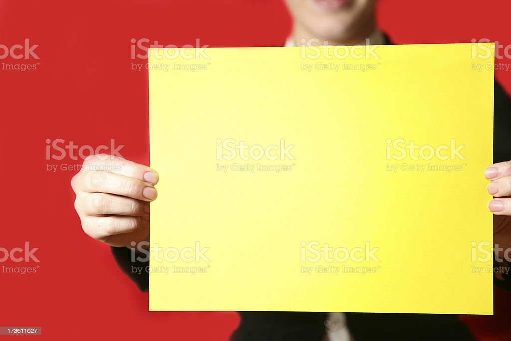 Woman holding out a blank yellow sign. stock photo