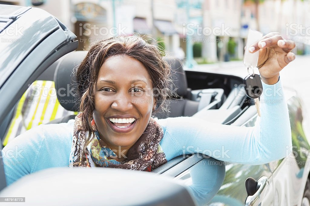Woman holding out car key from her new convertible stock photo