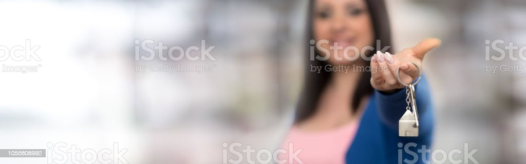 Woman holding out house keys stock photo