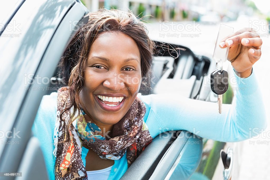 Woman holding out new car key for her convertible stock photo