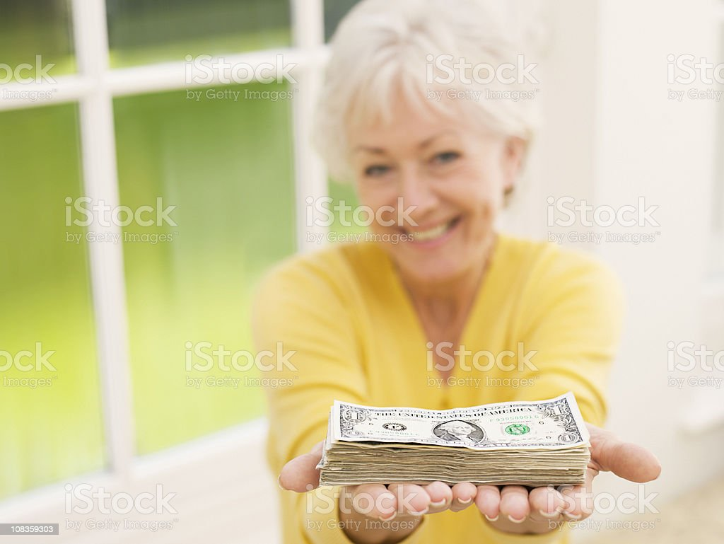 Woman holding out stack of one dollar bills royalty-free stock photo