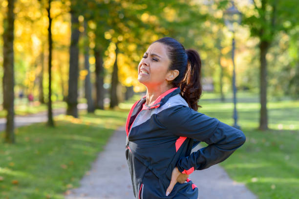 woman holding painful back in park - low section stock photos and pictures