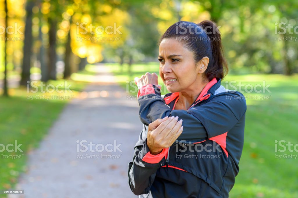 Woman holding painful elbow in park stock photo