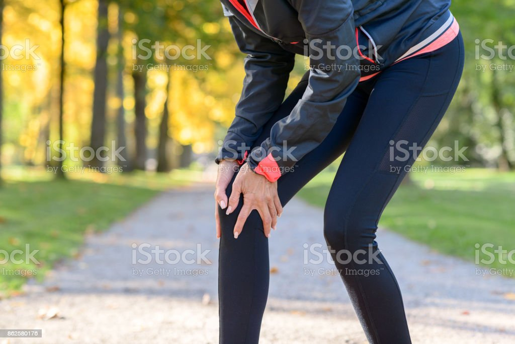 Woman holding painful knee in park stock photo