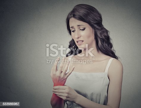 668285874istockphoto Woman holding painful wrist. Negative face expression 533986982