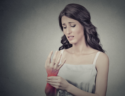 istock Woman holding painful wrist. Negative face expression 533986982