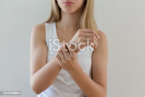 668285874 istock photo Woman holding painful wrist 1045269904