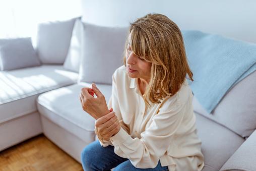 istock Woman holding painful wrist 1153388652