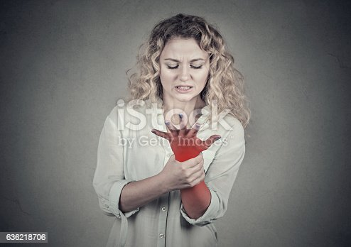 668285874istockphoto Woman holding painful wrist. Sprain pain in red 636218706