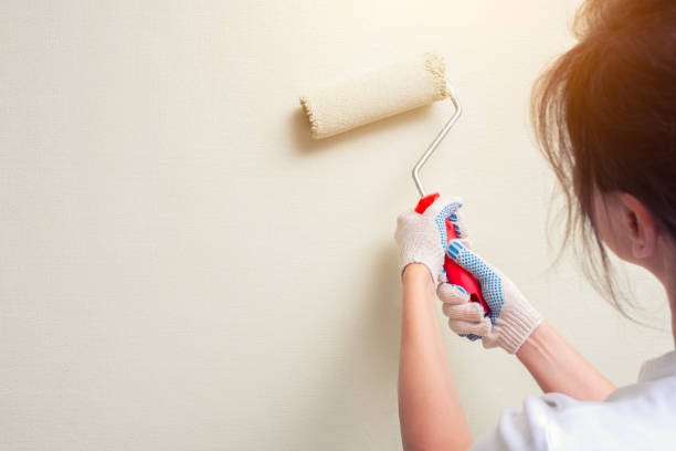 woman holding paint roller stock photo