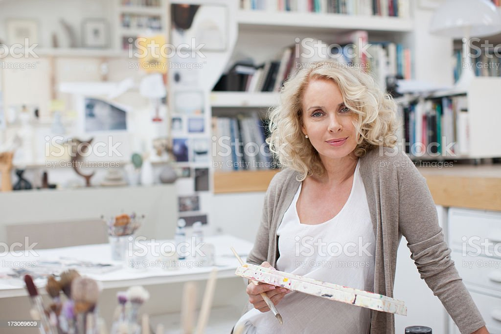 Woman holding paintbrush and palette in art studio stock photo