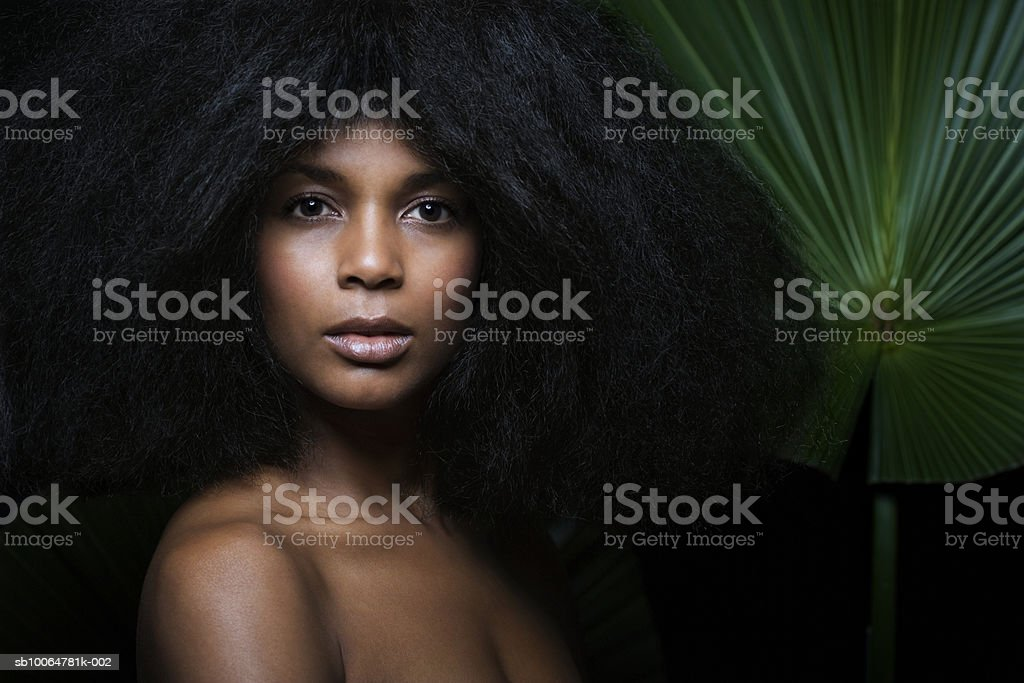 Woman holding palm leaf, close-up, portrait royalty-free stock photo