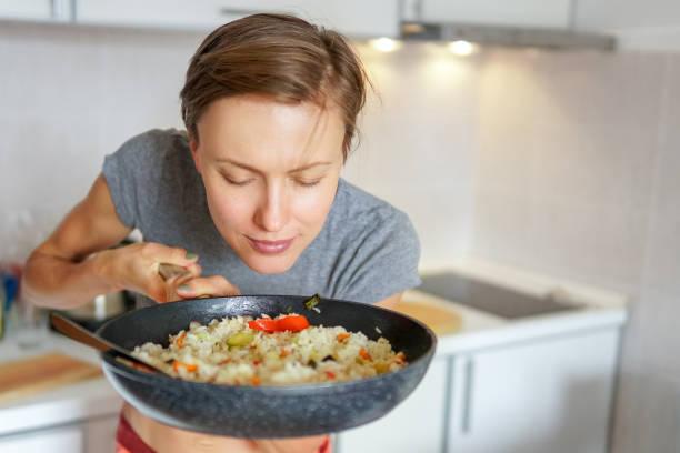 mujer sosteniendo la bandeja con arroz y vegetales - arroz comida básica fotografías e imágenes de stock