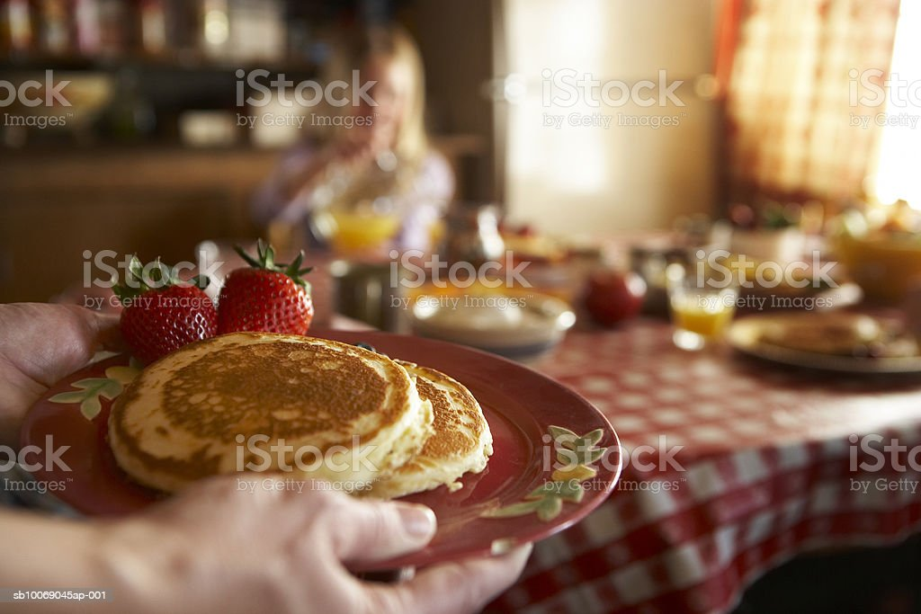 Woman holding pancakes with strawberries, girl in background having breakfast 免版稅 stock photo