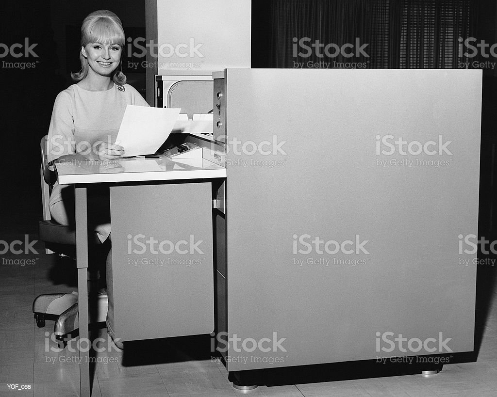 Woman holding paper and sitting at desk royalty-free stock photo