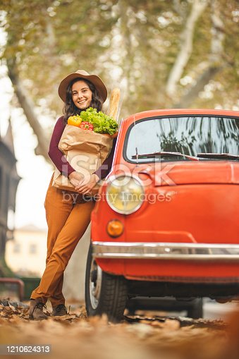Happy woman holding paper bag full of fresh groceries and standing near her red car