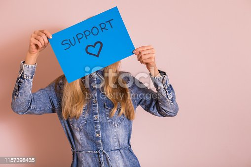 Woman holding paper with word support and heart shape while standing in front of the wall.