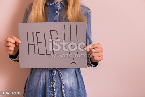 Woman holding paper with word help and sad face while standing in front of the wall.