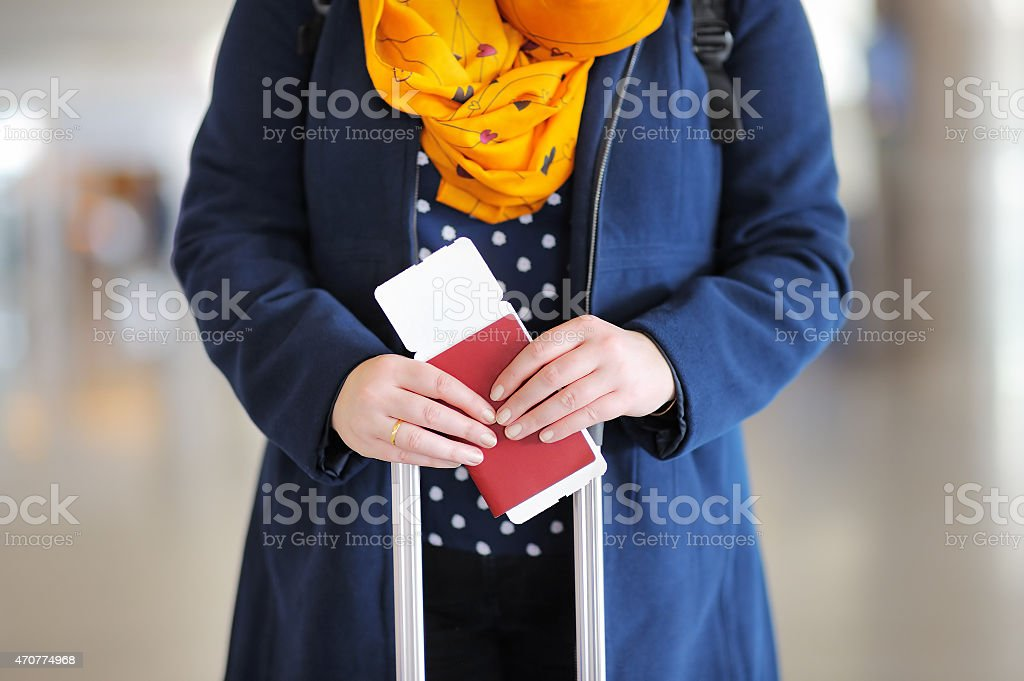 Woman holding passport and boarding pass stock photo