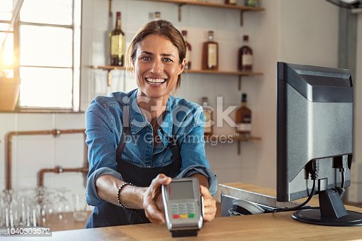 istock Woman holding payment machine 1040303572