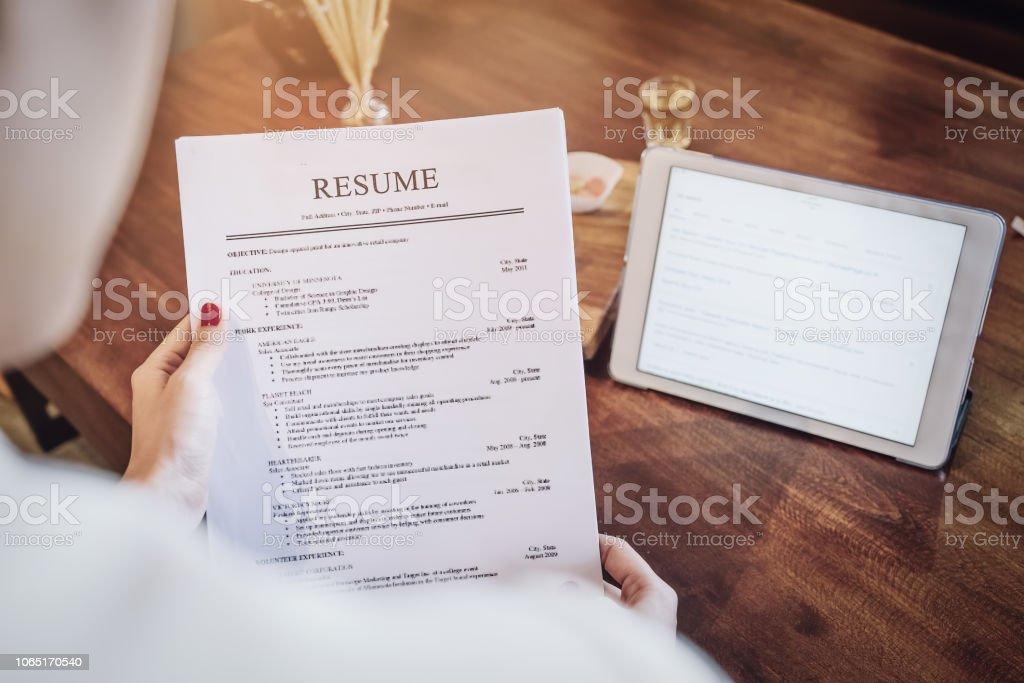 Frau hält Stift über Lebenslauf Anwendung mit Smartphone und Computer Laptop zur Jobsuche online Internet verwenden. Bewerbung für einen Job-Konzept. – Foto