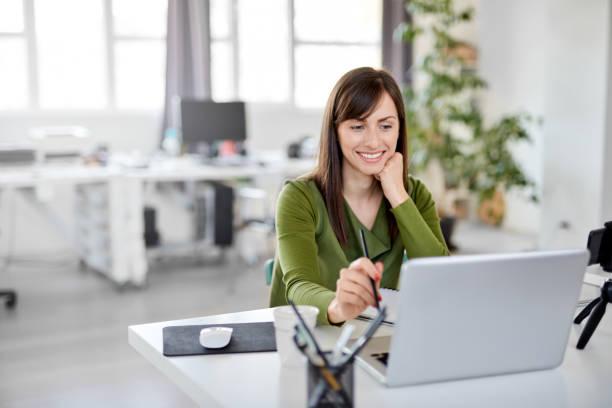 Frau hält Bleistift einen Blick auf Laptop, während im Büro sitzen. – Foto