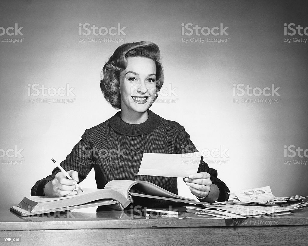 Woman holding pencil and paper, open book in front of her 免版稅 stock photo