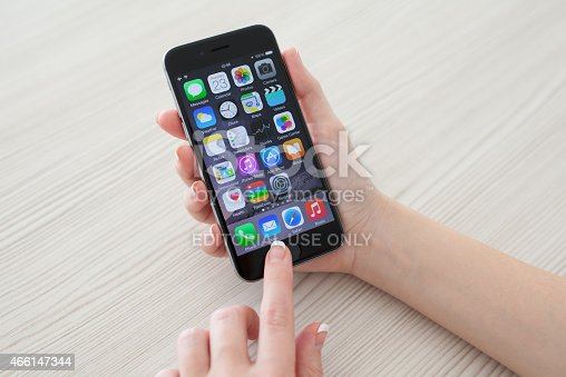 istock Woman holding phone iPhone 6 Space Gray over the table 466147344