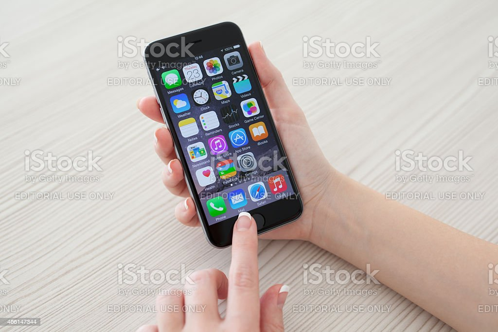 Woman holding phone iPhone 6 Space Gray over the table stock photo
