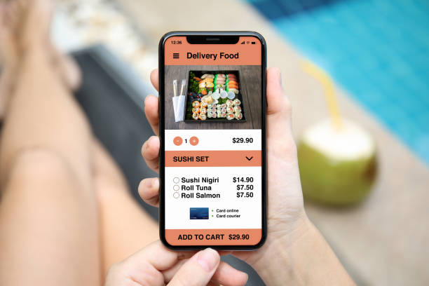woman holding phone with app delivery sushi food on screen - food delivery стоковые фото и изображения