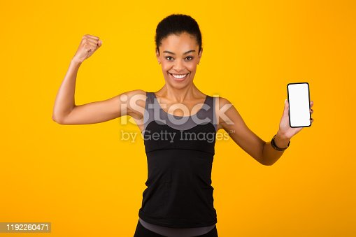 1159261513 istock photo Woman Holding Phone With Blank Screen Showing Biceps, Studio Shot 1192260471