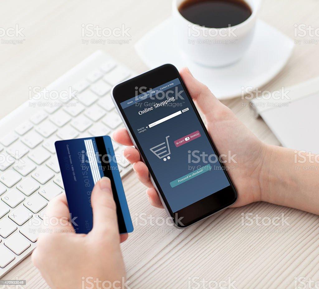 Frau hält Smartphone mit online-shopping mit Kreditkarte und  – Foto