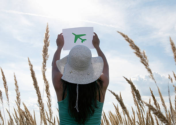 woman holding picture of airplane in sky - sustainable travel stockfoto's en -beelden