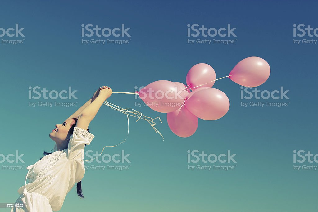 woman holding pink balloons stock photo