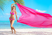istock Woman holding pink fabric in wind on the tropical beach 472332834