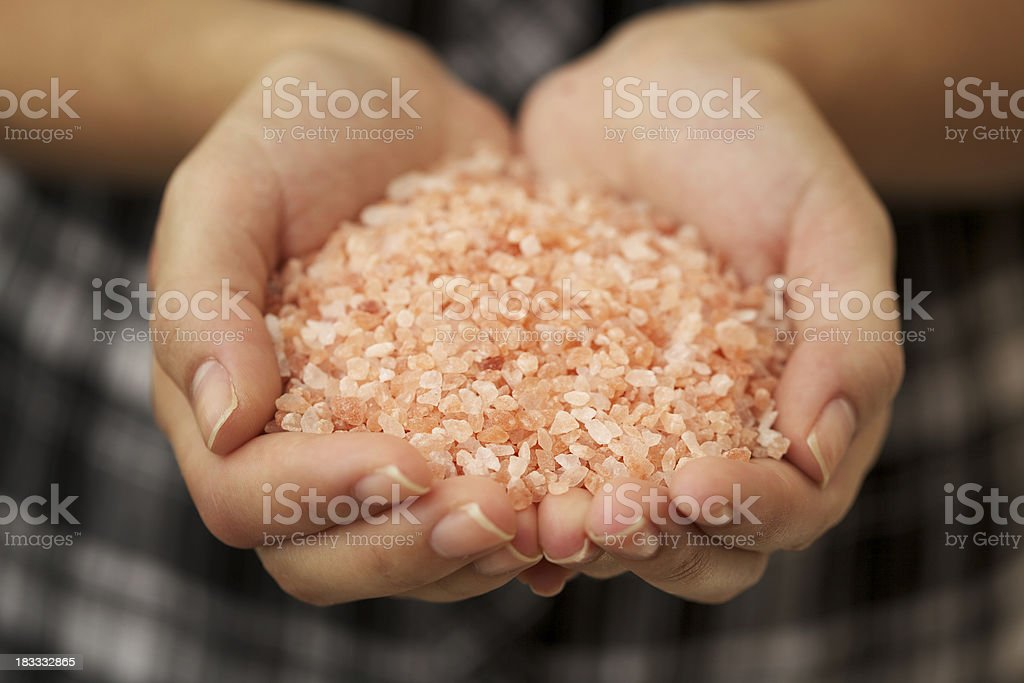 Woman holding pink Himalayan salt in her hands stock photo