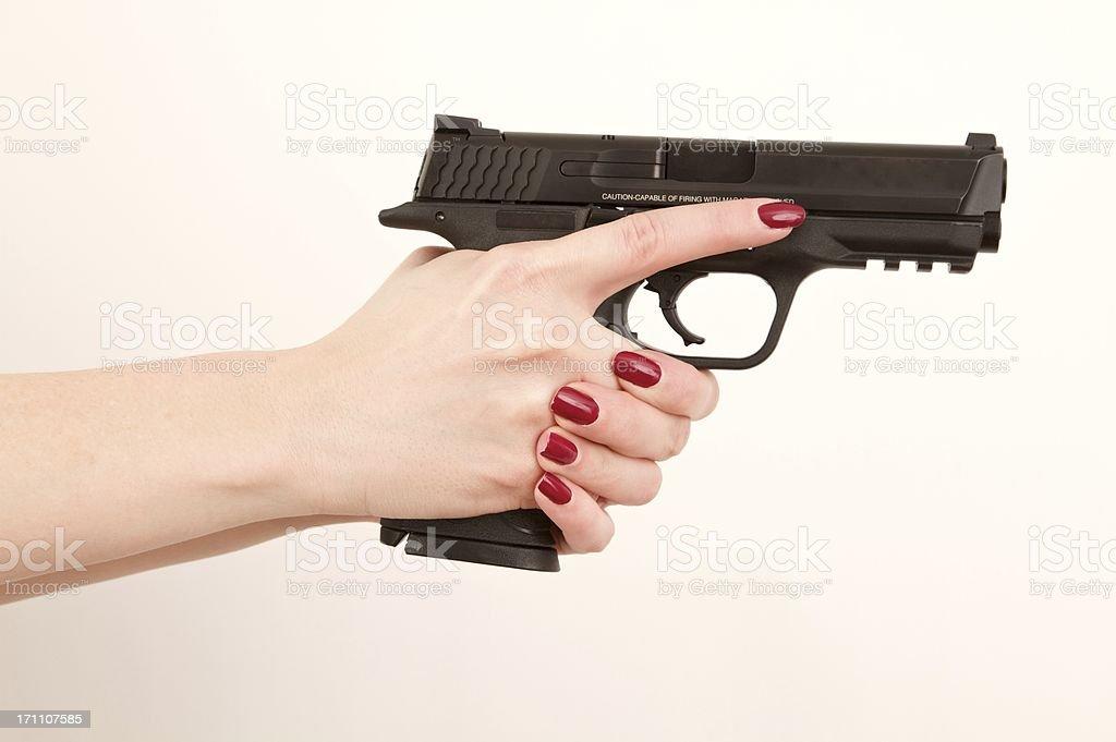 Woman holding pistol, finger off trigger stock photo
