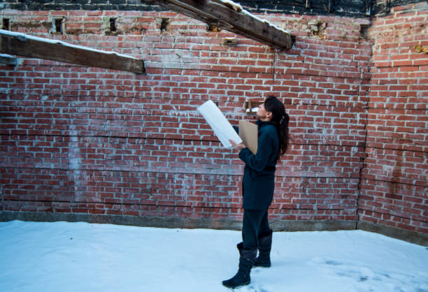 Woman holding plans looking up at old brick building to renovate stock photo