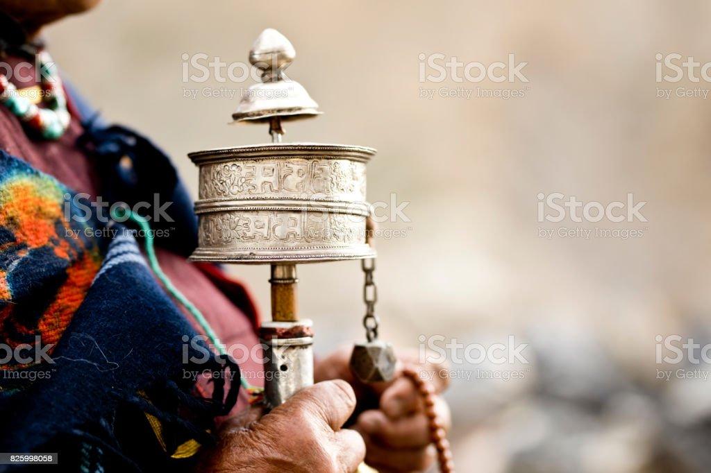 Woman holding prayer wheel and beads stock photo