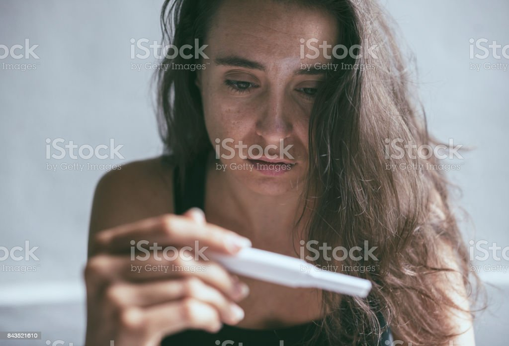 Woman holding pregnancy test with depressed worried face expression stock photo