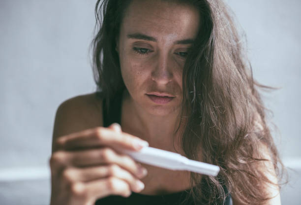 woman holding pregnancy test with depressed worried face expression - family planning stock photos and pictures