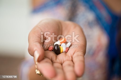 Woman holding pills on palm of her hand