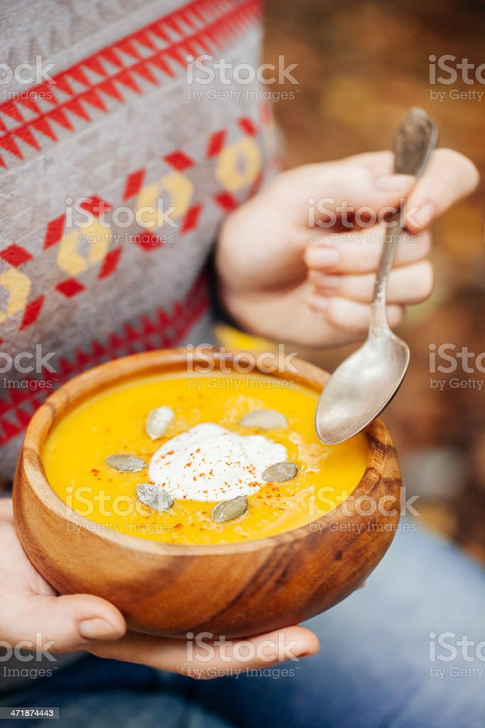 Woman holding pumpkin soup in a rustic bowl outside stock photo