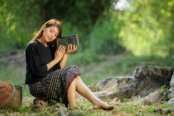 frau hält radio in wiese - schönen thai-frau ist sehr glücklich, thailand kultur, thailand buautiful bauer - radio kultur stock-fotos und bilder