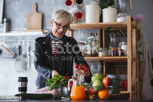 Mature woman in leather jacket standing by the kitchen counter, unpacking groceries from reusable cotton string bag after shopping.