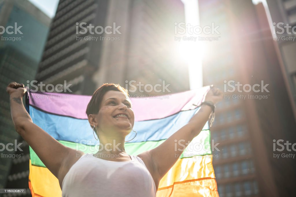 Woman holding rainbow flag with arms open during LGBTQI parade